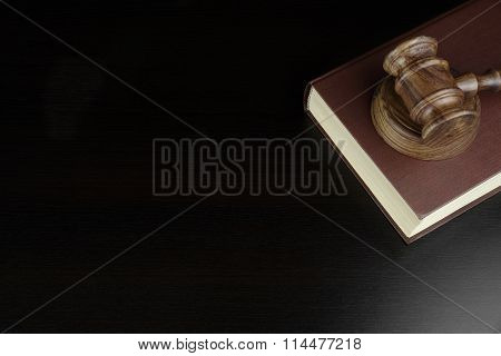 Judges Or Auctioneers Gavel And Red Book On Black Table