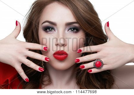 Close-up of a beautiful women holding finger on her red lips isolated on the white. Sexy Beauty Girl