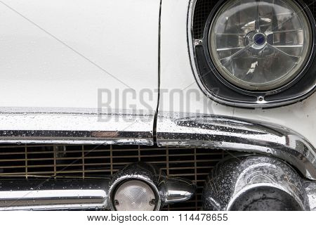 Closeup of front of vintage 1950's automobile with grill and headlamps