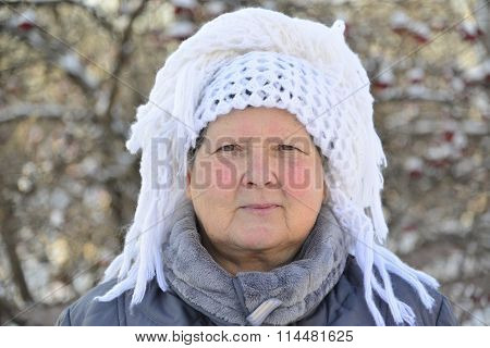 elderly woman in  white knitted shawl on her head is about Rowan