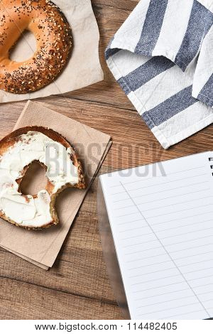 A bagel with cream cheese and a bite taken out. With a towel and note pad on a rustic wood desk. High angle view in vertical format,