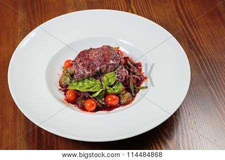 Baked meat with cherry tomatoes and basil sauce