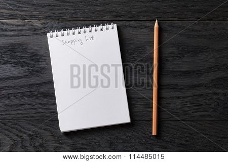 shopping list phrase in notepad on gray wood table