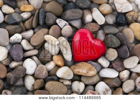Red heart on pebbles background