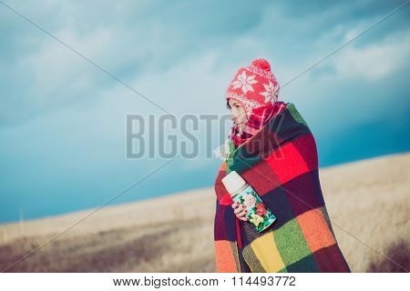 Nomad woman posing outdoor, wrapped around in a blanket