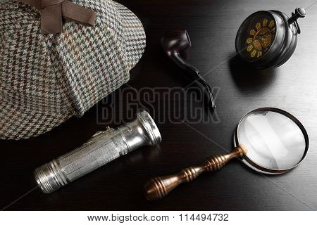 Deerstalker Hat Old Key Vintage Magnifying Glass Smoking Pipe And Flashlight On The Black Wooden Table Background. Overhead View.