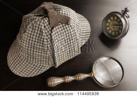 Deerstalker Hat,  Vintage Clock And Magnifier On Black Table