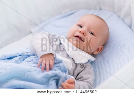 Baby Boy In A Crib Under Knitted Blanket