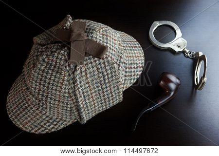 Sherlock Deerstalker Hat,  Handcuffs And Smoking Pipe On Black Table