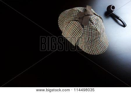 Sherlock  Deerstalker Hat And Pipe On The Black Wooden Table