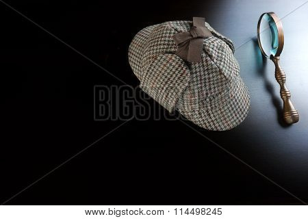 Deerstalker Hat And Vintage Magnifying Glass On The Black Wooden Table Background. Overhead View. Investigation Concept.