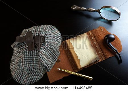 Private Detective Tools On The Black Wood Table Background. Deerstalker Hat Opened Notebook With Blank Brown Page Pipe Magnifying Glass Fountain Pen