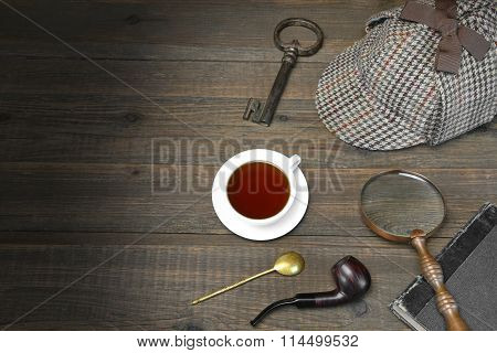 Private Detective Tools On The Wood Table Background. Deerstalker Cap, Magnifier, Old Key, Tea Cup, Notebook And Smoking Pipe On The Wood Table, Top View