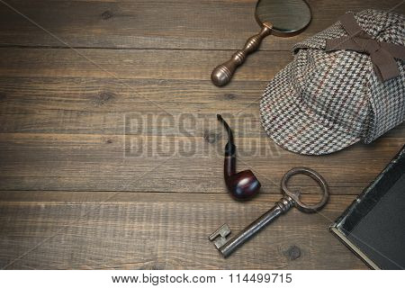 Private Detective Tools On The Wood Table Background. Deerstalker Cap Old Key And Book Tobacco Pipe Vintage Magnifying Glass