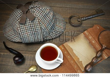 Private Detective Tools On The Wood Table Background. Deerstalker Cap Magnifier Key Cup Notebook Smoking Pipe.