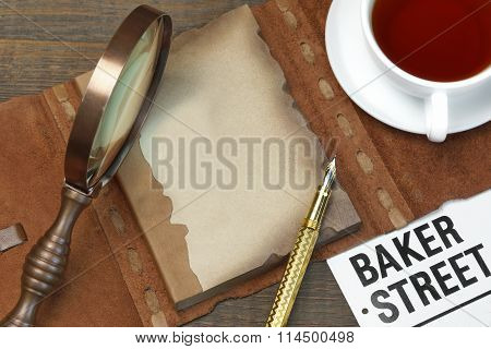 Private Detective Tools On The Wood Table Background. Magnifying glassTea Cup Notebook With Blank Brown Page Pen