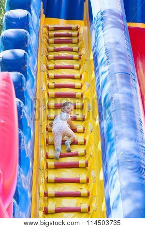 Three Year Old Girl Climbs On A Big Inflatable Trampoline