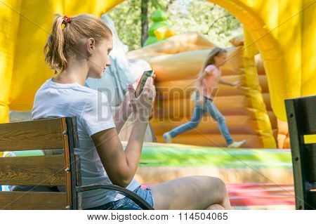 Young Mother With A Child At The Phone Waiting Inflatable Trampolines