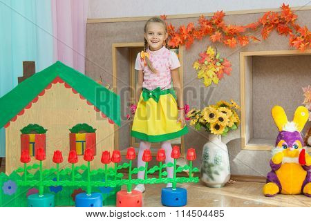 Six Year Old Girl Stands In The Scenery Of A Country House On The Matinee In Kindergarten