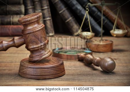 Gavel, Old Book, Magnifier And  Scale On The Wooden Table
