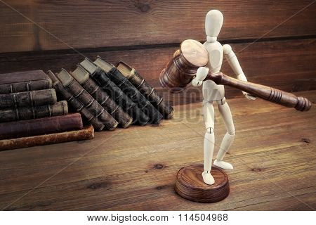 Wooden Figurine With Judges Gavel On The Wood Table