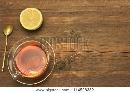 Transparent Glass Teacup And Gold Teaspoon On Rough Wood Table