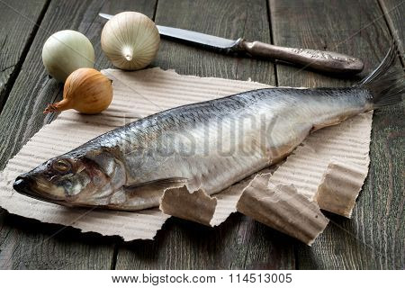Salted Herring On The Paper, Onion And Knife On A Table