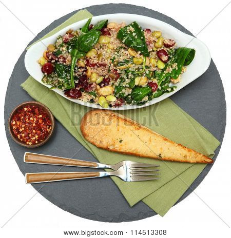 Quinoa Salad with cranberry, spinach, beans in bowl with garlic bred and crushed red pepper spices.