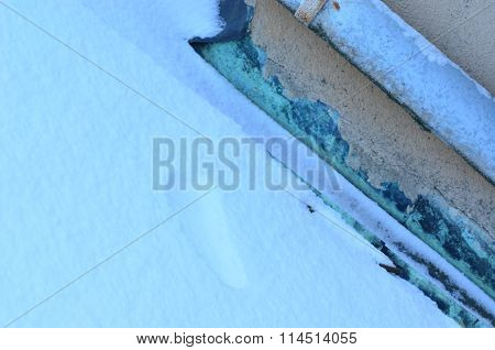 Snow-covered roof and tracks in snow .