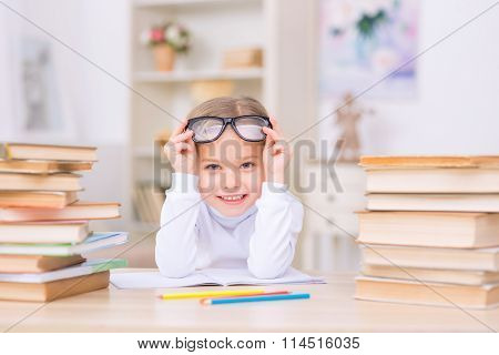 Little positive girl is at the desk with many books.