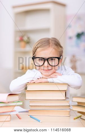 Little girl leaning on a pile of books.