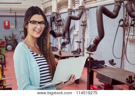 Pretty girl with laptop against various eqipments and pipes in factory