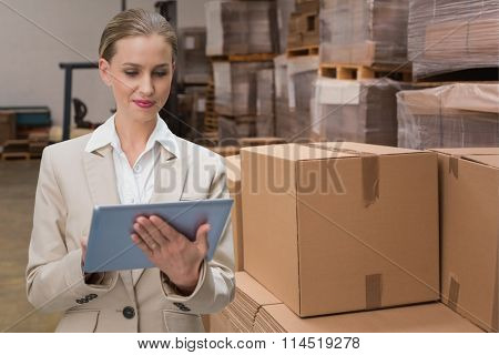 Thoughtful stylish businesswoman looking at tablet against forklift in a large warehouse