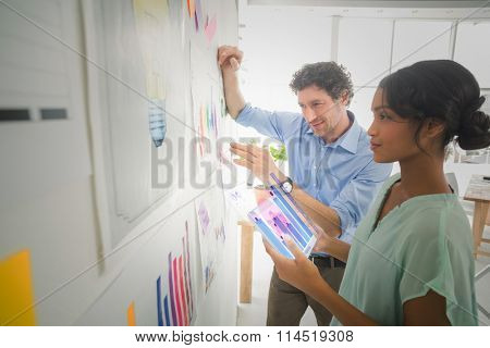 Percentages graphical representation against business team analyzing charts together