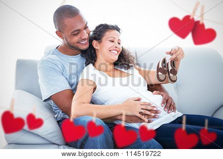 Couple with baby shoes against hearts hanging on a line