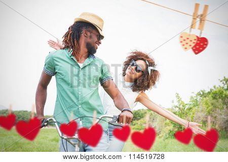 Young couple on a bike ride against hearts hanging on a line