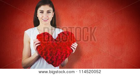Woman holding heart shape cushion against red background