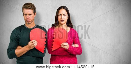 Portrait of serious couple holding cracked heart shape against white and grey background