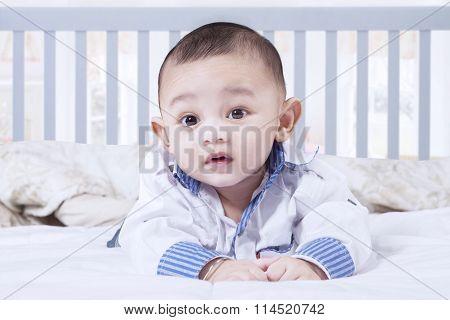 Adorable Baby Boy Lying On Bedroom
