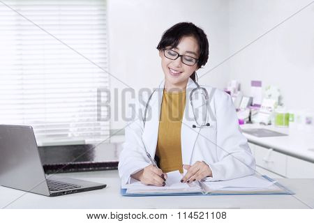 Attractive Female Doctor Working On Table
