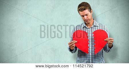 Sad man holding a broken card against blue background