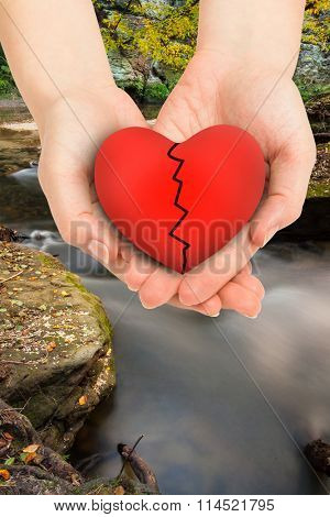 Couple holding broken heart in hands against rapids flowing along forest