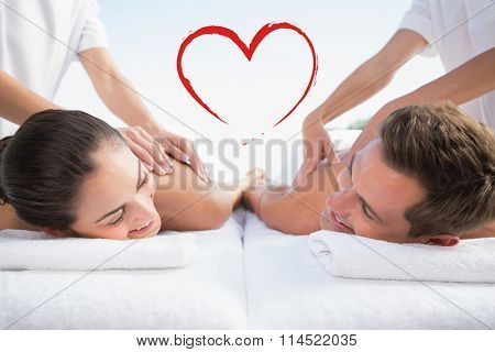 Peaceful couple enjoying couples massage poolside against heart