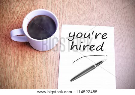 Coffee On The Table With Note Writing You're Hired