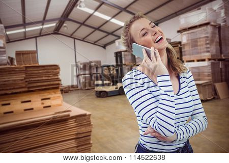 Pretty girl with phone against forklift in a large warehouse
