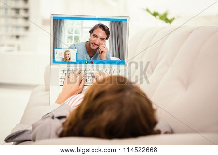 Closeup of beautiful woman smiling at home against woman using laptop while lying on sofa