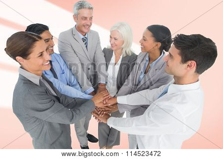 Executives holding hands together in office against red vignette