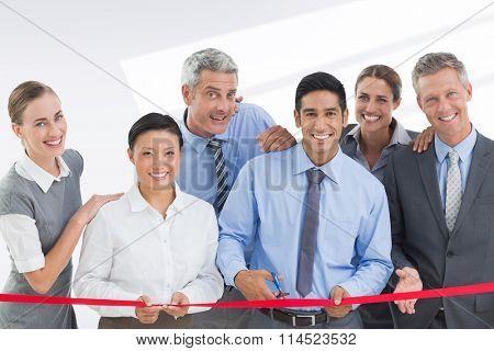 Business man cutting red strip against grey vignette