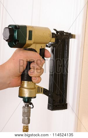 Carpenter using nail gun to complete door framing trim