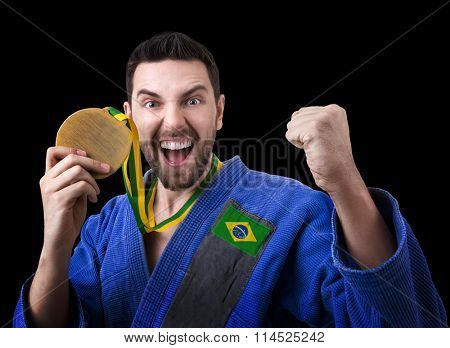 Brazilian judoka fighter man holding a medal isolated on black background